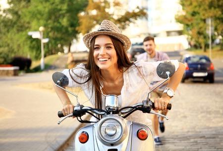 ライフスタイル: ハンサムな男と若い女性は、オートバイに乗る