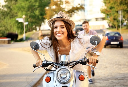 Handsome guy and young woman ride motorcycles