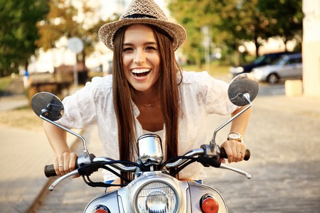 Portrait of a beautiful girl sitting on a silver retro scooter, smiling and looking at the camera