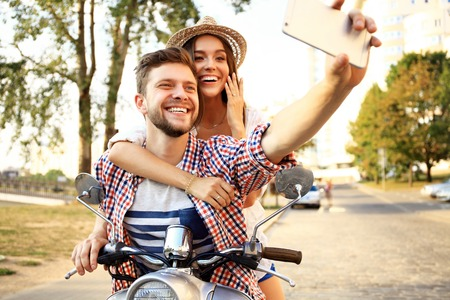 beard woman: Happy couple on scooter making selfie photo on smartphone outdoors