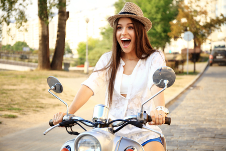 Portrait of a beautiful girl sitting on a silver retro scooter Stock Photo