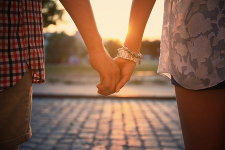 holding hands while walking: Closeup of loving couple holding hands while walking at sunset
