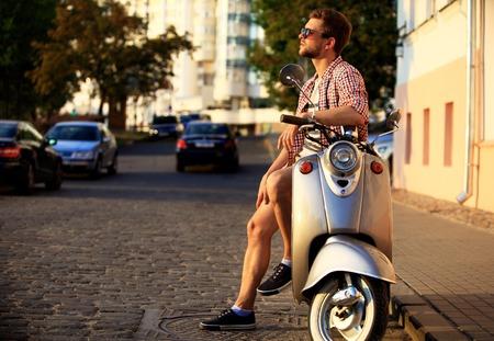 vespa piaggio: moda giovane in sella a uno scooter d'epoca in strada Archivio Fotografico
