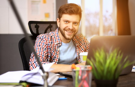 thirties: Confident young man working on laptop while sitting at his working place in office