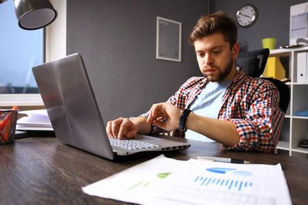 Business and time management concept. Stressed zakenman op zoek naar polshorloge. Bezorgd gezichtsuitdrukking. menselijke emotie