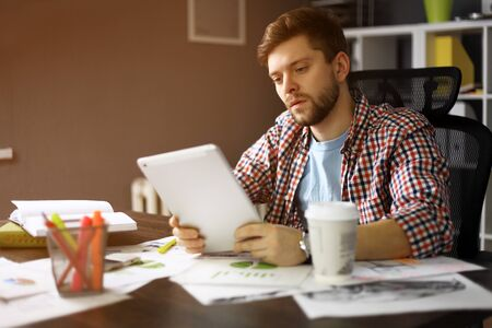 personas leyendo: persona de sexo masculino pensativo mirando a la pantalla de la tableta digital mientras se está sentado en el interior de alojamiento moderno en la mesa Foto de archivo