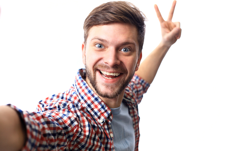 persona alegre: Hombre joven feliz que toma una foto selfie. Aislado en el fondo blanco Foto de archivo