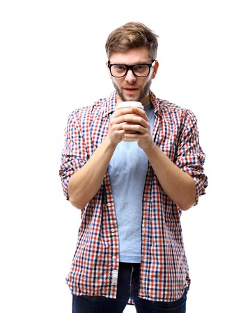 resting: Handsome young man holding coffee cup and smiling while standing against white background