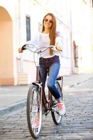 Ocio urbano - mujer joven y la bicicleta en la ciudad Foto de archivo - 53535951