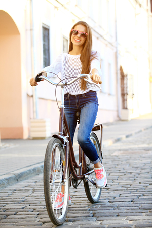 Urban leisure - young woman and bike in city Stock Photo