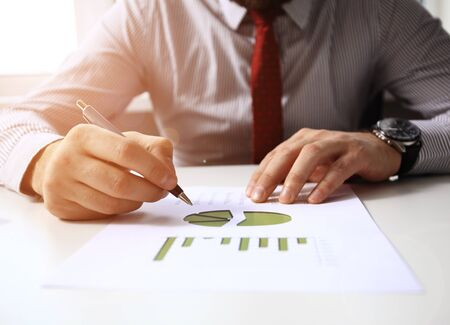 finance concept: Image of male hand pointing at business document during discussion at meeting Stock Photo