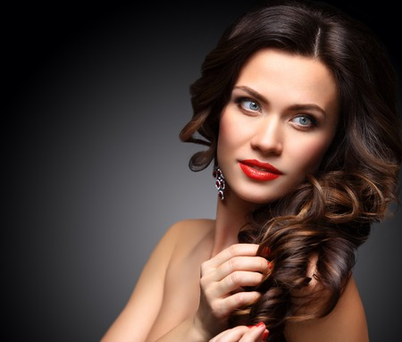 beauty eyes: Beauty Model Woman with Long Brown Wavy Hair. Healthy Hair and Beautiful Professional Makeup. Red Lips and Smoky Eyes Make up. Gorgeous Glamour Lady Portrait