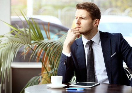 moneymaker: Portrait of handsome successful man drink coffee and look to the digital tablet screen sitting in coffee shop, business man having breakfast Stock Photo