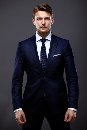 standing businessman: Cool young businessman standing on grey background Stock Photo