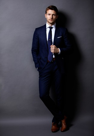 Cool young businessman standing on grey background Archivio Fotografico