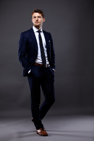 Cool young businessman standing on grey background Stock Photo