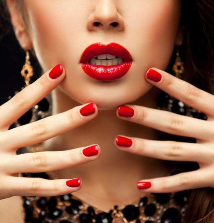 赤いセクシーな唇と爪のクローズ アップ。口を開けてください。マニキュア、化粧。概念を確認します。黒の背景に分離された美少女モデルの顔の