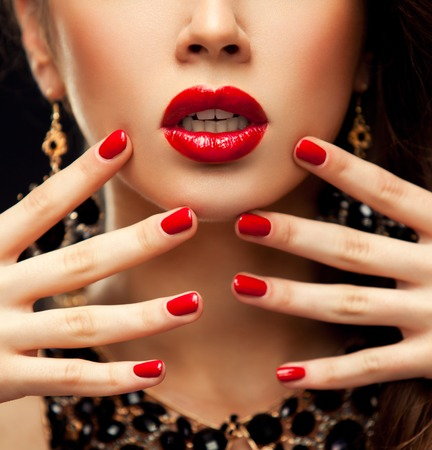 Red Sexy Lips and Nails closeup. Open Mouth. Manicure and Makeup. Make up concept. Half of Beauty model girl's face isolated on black background