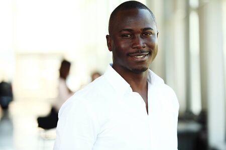 hombres negros: Retrato de sonriente hombre de negocios estadounidense con los ejecutivos que trabajan en segundo plano
