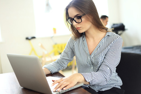 Ritratto di una donna d'affari giovane con laptop in ufficio