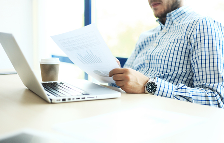 analyze: Business man working at office with laptop and documents on his desk. Analyze plans, papers, hands keyboard. Blurred background, film effect