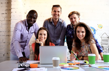 Portrait of happy young people in a meeting looking at camera and smiling. Young designers working together on a creative project.