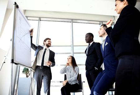Fröhlich Geschäftsmann ein neues Business-Projekt mit den Mitgliedern seines Teams diskutieren Standard-Bild - 62591587