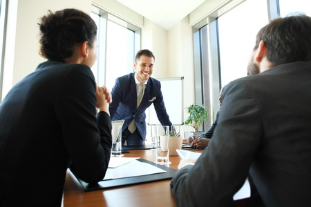 planning strategy: Young man presenting is ideas to colleagues during meeting in conference room. Leader showing business plan to colleagues during a meeting. Stock Photo