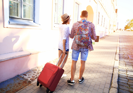 Two travelers on vacation walking around the city with luggage Foto de archivo
