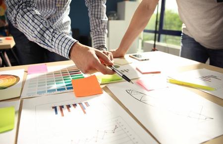 비즈니스: 비즈니스 팀 브레인 스토밍. 마케팅 계획 조사. 테이블, 노트북 및 휴대 전화에 대한 서류