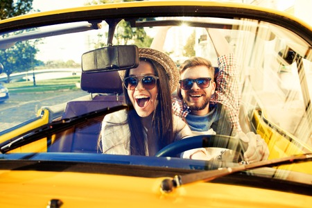 Happy to travel together. Joyful young couple smiling while riding in their convertible Banque d'images