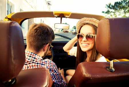 loaning: handsome couple looking at camera sitting in a car, view from rear seat Stock Photo