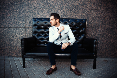 mature man: Young handsome bearded stylish man sitting on comfortable leather sofa outdoors