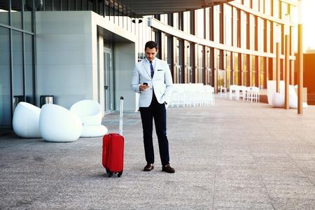 hospedaje: Joven hombre de negocios feliz que viaja toma de la palabra después de llegar al hotel fuera con su equipaje. viajero sonriente que usa el teléfono inteligente