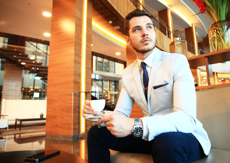 successful man: Portrait of handsome successful man drink coffee sitting in coffee shop, business man having breakfast at hotel lobby Stock Photo