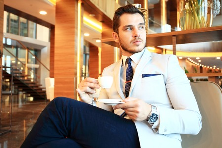moneymaker: Portrait of handsome successful man drink coffee sitting in coffee shop, business man having breakfast at hotel lobby Stock Photo