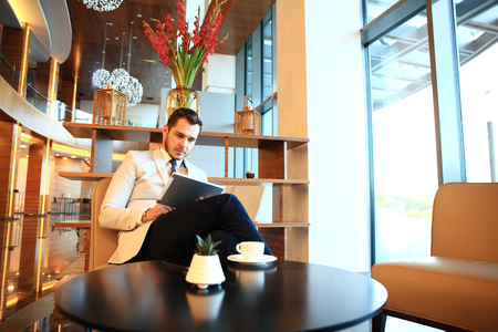 moneymaker: Portrait of handsome successful man drink coffee and look to the digital tablet screen sitting in coffee shop, business man having breakfast at hotel lobby