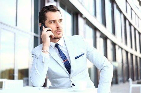 phone professional: Man on smartphone - young business man talking on smart phone. Casual urban professional businessman using mobile cell phone smiling happy Stock Photo