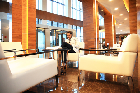 Portrait Of Happy Young Businessman Sitting On Sofa In Hotel Lobby Stock  Photo   65006190