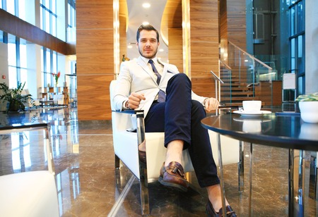 businessman waiting call: Portrait of happy young businessman sitting on sofa in hotel lobby