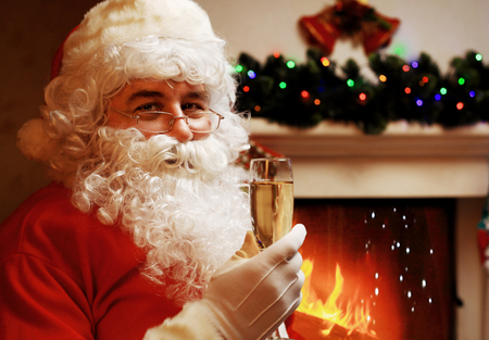merriment: Santa Claus with a glass of sparkling wine champagne near a Christmas tree