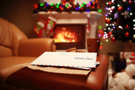 write a letter: Letter to Santa Claus near the gift and candles. Home decoration. Stock Photo