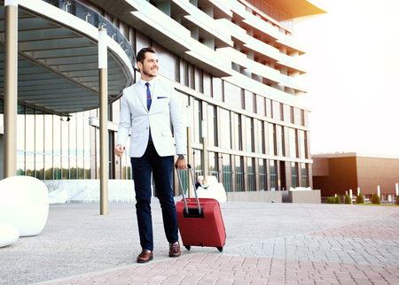 Businessman walking to hotel lobby. Full length portrait of young executive with a suitcase.