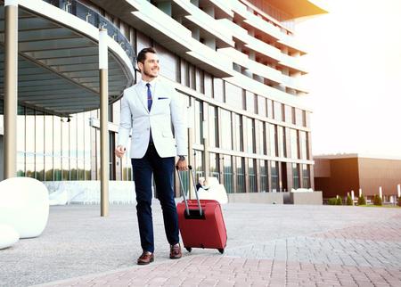 Homme d'affaires qui se promène dans le hall de l'hôtel. Portrait complet de jeune exécutif avec une valise. Banque d'images - 65005966