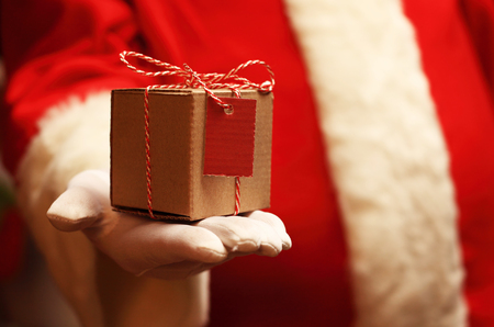 xmass: Santa Claus gloved hands holding giftbox. Christmas