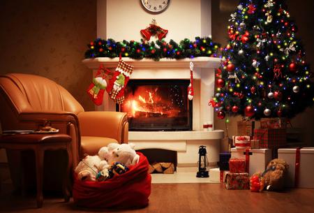 Weihnachtsbaum und Weihnachtsgeschenk-Boxen im Inneren mit einem Kamin. Weihnachten Wohnzimmer mit Kamin und Sessel