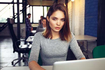 woman in office: Portrait of a serious businesswoman using laptop in office. Beautiful hipster woman taking notes at modern office