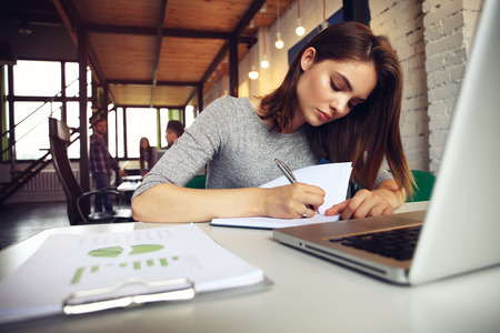 Retrato de una mujer de negocios serio usando la computadora portátil en la oficina. Hermosa mujer inconformista tomar notas en la oficina moderna