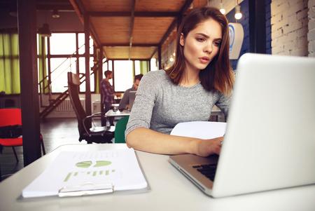 Portret van een ernstige zakenvrouw met behulp van laptop op kantoor. Mooie hipster vrouw het maken van aantekeningen op modern kantoor