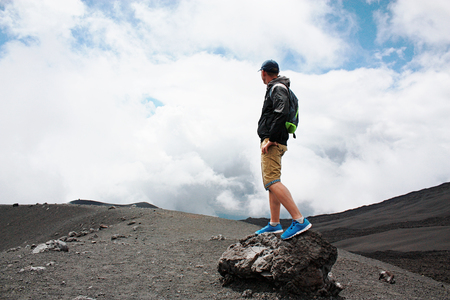 Encouraged man on the hill is looking on Etna volcano eruption. Etna, Italy.